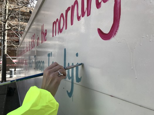 Francesca painting coloured words onto the hoardings
